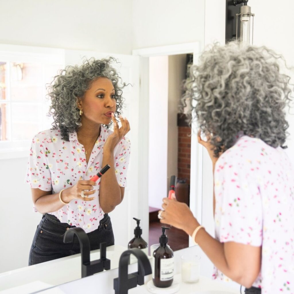 POC woman with grey curly hair, reapplying her lipstick in a beautifully aesthetic all-white bathroom.