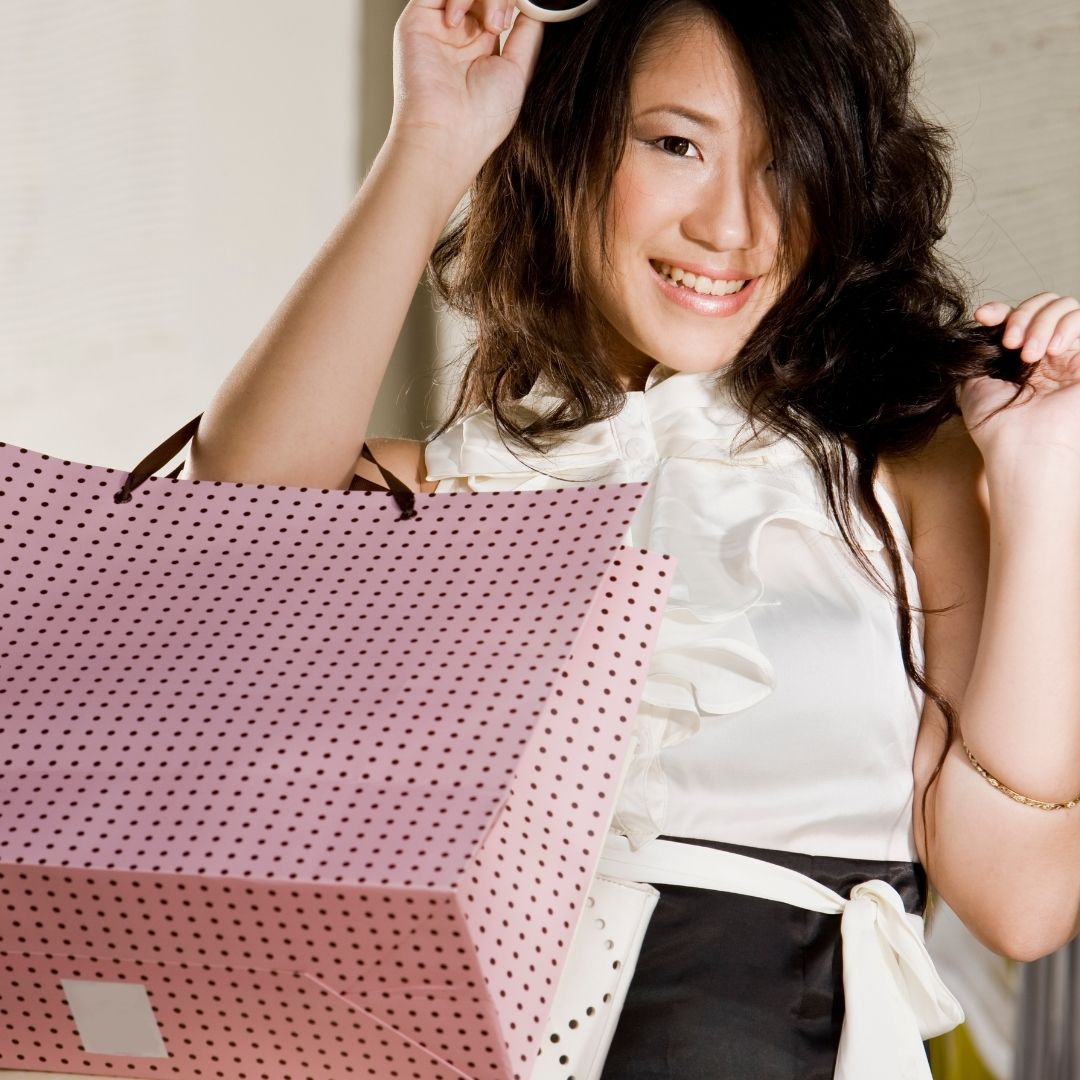Woman holding up her paper shopping bags high, looking very proud and excited for the clothing item in her bags.
